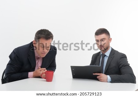 Senior and junior business people in elegant suits sitting at desk, boss looking in red cup, employee holding clipboard isolated on white background