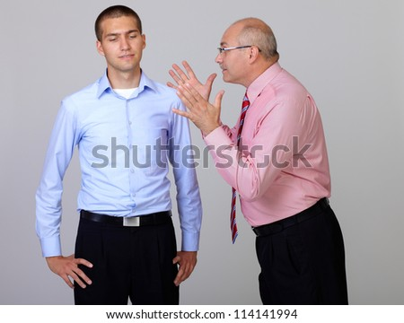 Senior and junior businessman discuss and argue over something during their meeting, isolated on grey - stock photo