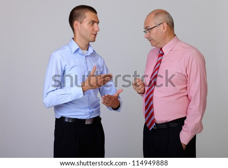 Senior and junior businessman discuss something during their meeting with hands in pockets, isolated on grey - stock photo