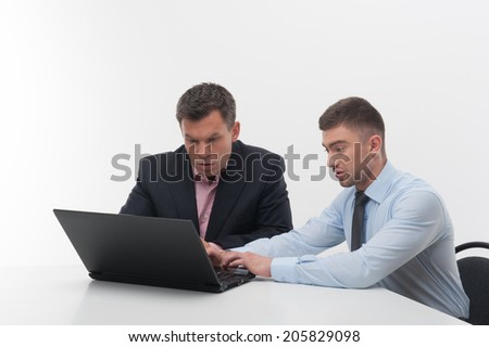 Senior and junior handsome business people discuss something sitting at desk, employee showing something on laptop to his boss, isolated on white