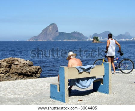 Senior and man contemplating the sea with The Sugar Loaf in the background, in Rio de Janeiro - stock photo