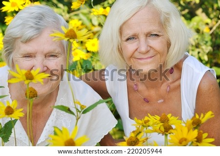 Senior and mature women in garden full of flowers. MANY OTHER PHOTOS FROM THIS SERIES IN MY PORTFOLIO. - stock photo