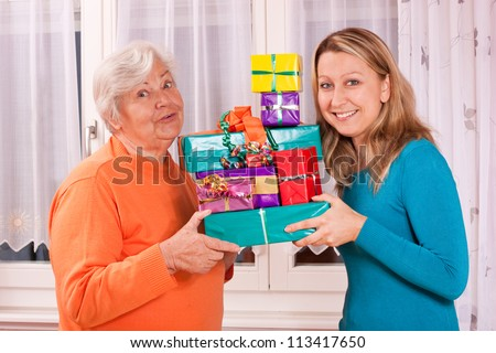 senior and young female holding presents