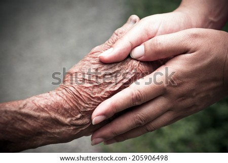 Senior and young holding hands - stock photo