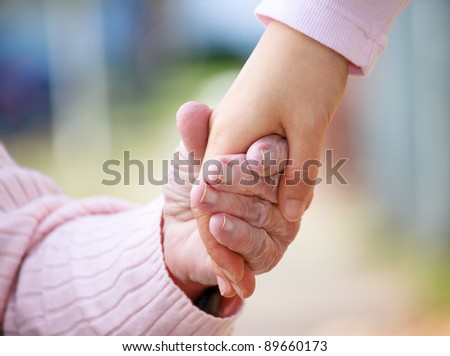 Senior and young holding hands outside - stock photo