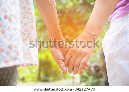 Senior and young holding hands with vintage color tone - stock photo