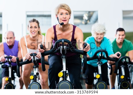 Senior and young people spinning on fitness bike in gym doing endurance and cardio training, the instructor is leading them on - stock photo