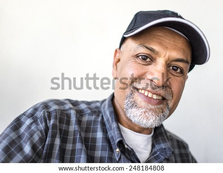Senior Arabic Pakistani man portrait with hat - stock photo