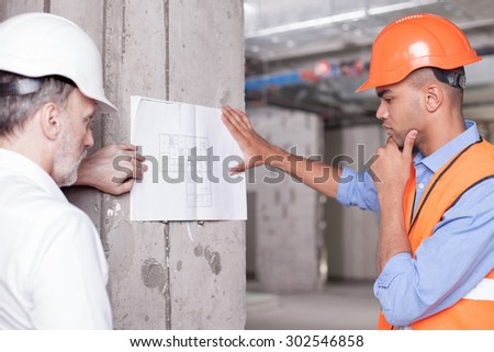 Senior architect and young foreman are looking at the plan of building pensively. They are leaning a blueprint on the wall. The worker is touching his chin thoughtfully - stock photo