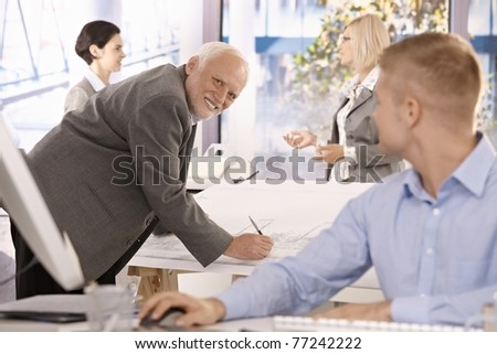 Senior architect at work, smiling at younger colleague, with team in office.? - stock photo