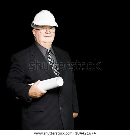 Senior architect in an architectural firm with all the expertise and knowledge of his years carries a blueprint as he goes about a building site inspection - stock photo