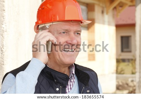 Senior architect standing in front of building, while using his mobile phone. Small business. - stock photo