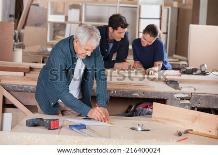 Senior architect working on blueprint with coworkers in background at workshop - stock photo