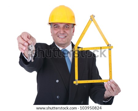 Senior architect yellow helmet holding wooden ruler folded in house shape and keys - over white background - stock photo