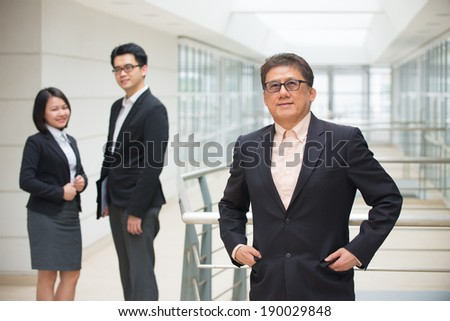 senior asian business ceo with team on background