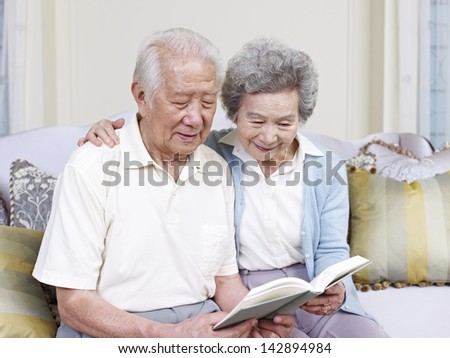 senior asian couple reading a book together at home. - stock photo