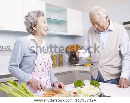 senior asian couple talking and laughing in kitchen. - stock photo