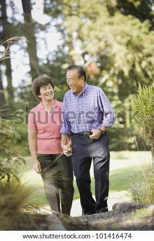 Senior Asian couple walking in woods
