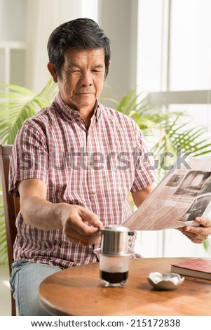Senior Asian man drinking coffee and reading morning newspaper - stock photo