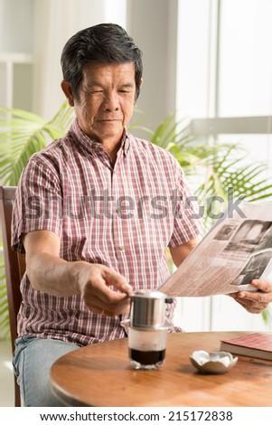 Senior Asian man drinking coffee and reading morning newspaper - stock photo