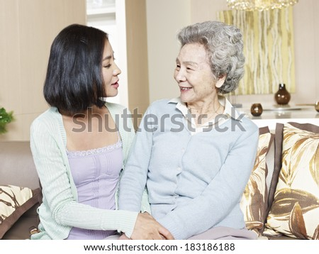 senior asian mother chatting with adult daughter at home - stock photo