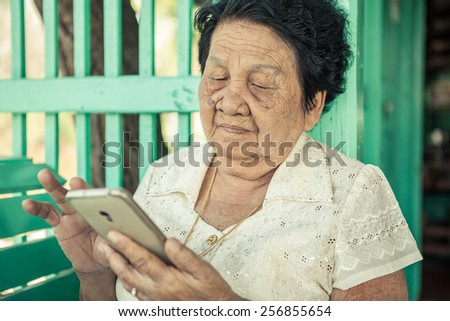 Senior asian woman  with smart phone - stock photo