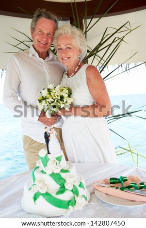 Senior Beach Wedding Ceremony With Cake In Foreground - stock photo