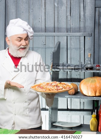 Senior bearded chef with pizza in white uniform with smiling face and hat on wooden background