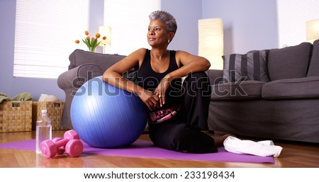 Senior Black woman sitting on floor with exercise equipment - stock photo