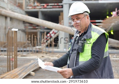 Senior Brigadier at construction site is inspecting ongoing production according to design drawing. - stock photo