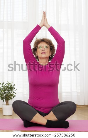 Senior brown haired woman  sitting on the parquet Floor and  exercising yoga at home. - stock photo