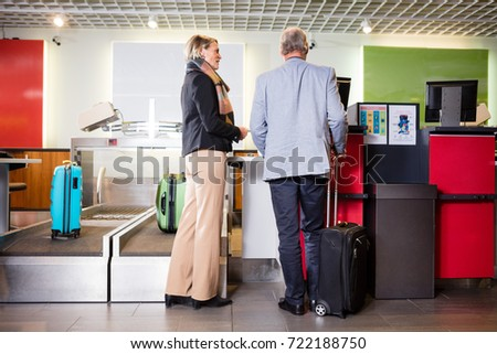 Senior Business Couple Standing At Airport Check-in Desk