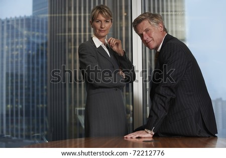 Senior business man and woman in a boardroom smiling looking at camera