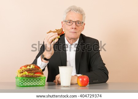 Senior business man eating his bread meal at the office - stock photo