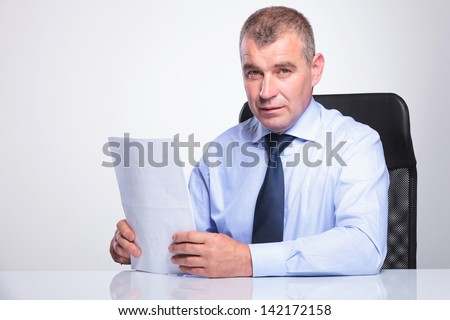 senior business man sitting at his office and holding some documents while looking at the camera. on gray background