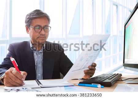 senior business man working on office table  with computer and business graph report ,writing and thinking solution planing - stock photo