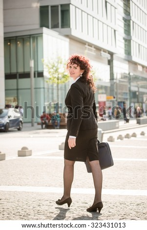 Senior business woman carrying laptop bag walking street turns over shoulder on photographer