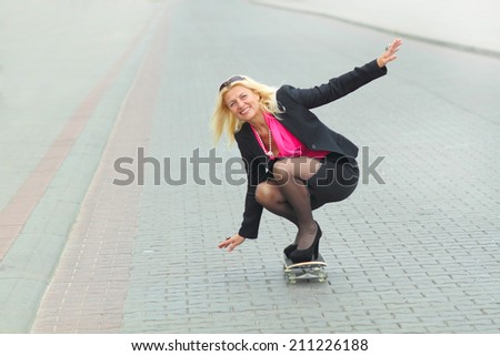 Senior business woman having fun on a skateboard outdoors - stock photo