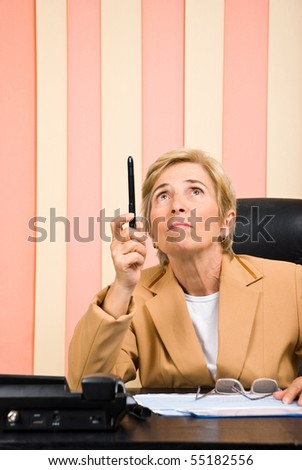 Senior business woman in office looking and pointing up with her pencil