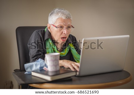 Senior business woman shocked with the content she finds on her laptop
