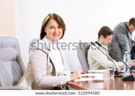 Senior business woman working with documents at the conference, on the table microphone stand - stock photo
