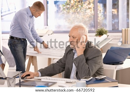 Senior businessman and young architect working in office, businessman talking on phone looking at computer screen, architect working on drawing table.?