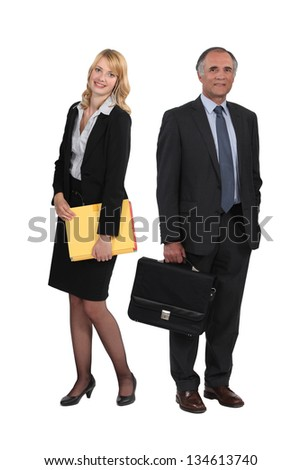 senior businessman and young assistant posing together