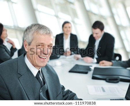 Senior businessman at a meeting smiling - stock photo
