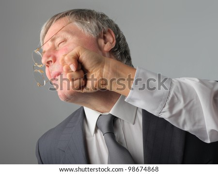 Senior businessman being punched in the face - stock photo