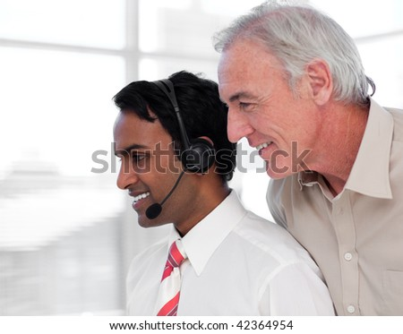 Senior businessman checking work in a call center - stock photo