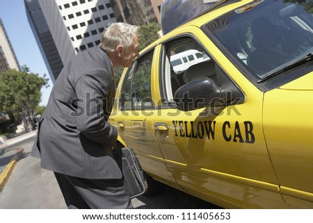 Senior businessman discussing his fare with a taxi driver