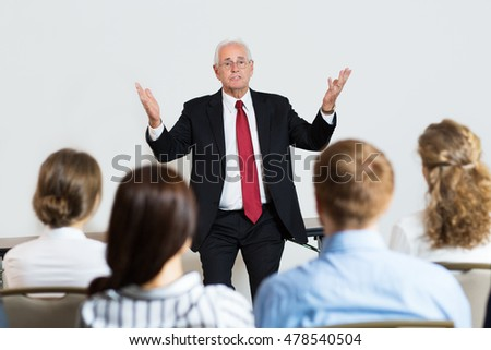 Senior Businessman Explaining Idea to His Colleagues at Conference