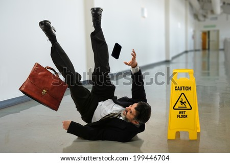 Senior businessman falling near caution sign in hallway - stock photo
