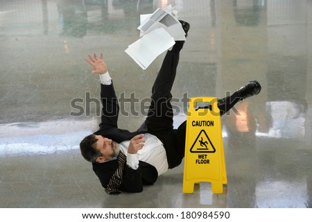 Senior businessman falling on wet floor in front of caution sign - stock photo